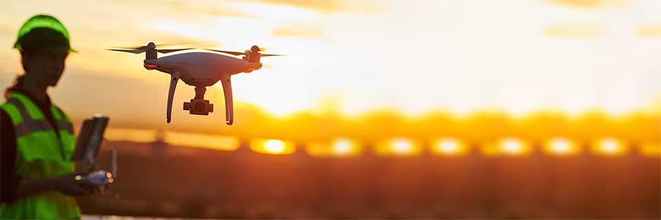Technikantin steuert eine fliegende Drohne