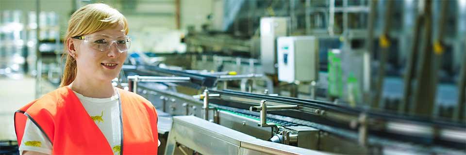 Technikantin mit roter Weste und Schutzbrille